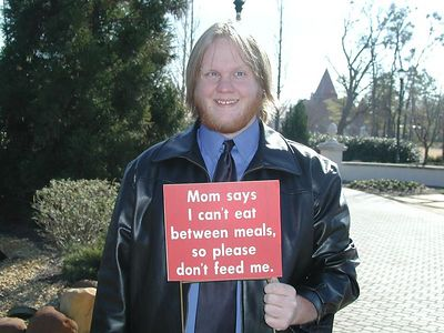 Ben with his eyes crossed, holding a sign that says 'Mom says I can't eat between meals, so please don't feed me'.